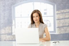 Happy businesswoman in sunny office. Happy businesswoman sitting with laptop computer in sunny office, smiling at camera royalty free stock images