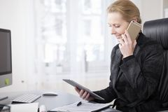 Happy Businesswoman with Tablet Talking on Phone. Close up Happy Businessman in Black Suit Looking at her Tablet Screen While Talking to Someone on Mobile Phone Stock Photo