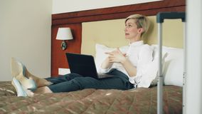 Happy businesswoman talking with family via online video chat using laptop computer lying on bed in hotel room. Travel. Happy cheerful businesswoman talking with stock footage