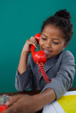 Happy businesswoman talking on land line phone. At desk against blue background Stock Images
