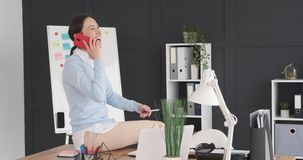 Happy businesswoman talking on mobile phone at office desk. Businesswoman having fun while talking on mobile phone at office desk stock video