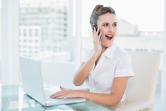 Happy businesswoman talking on the phone sitting Royalty Free Stock Images
