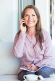 Happy businesswoman talking on the phone and writing in organize Royalty Free Stock Photo