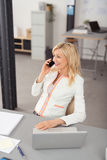 Happy Businesswoman Talking to Someone on Phone. Happy Blond Adult Businesswoman, Sitting at her Table with Laptop, Talking to Someone on Mobile Phone stock photography