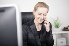 Happy Businesswoman Talking to Someone on Phone. Close up Happy Blond Businesswoman in Black Suit Talking to Someone Through Mobile Phone While Sitting at her Stock Image