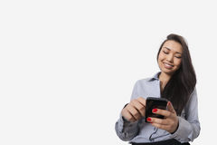 Happy businesswoman text messaging through smart phone against gray background Royalty Free Stock Photo