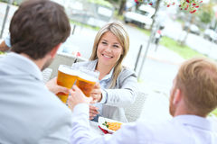 Happy businesswoman toasting beer glass with male colleagues at sidewalk cafe Stock Photo