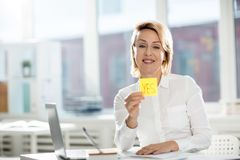 Saying yes. Happy businesswoman with toothy smile showing yellow notepaper with positive answer and looking at camera Royalty Free Stock Image