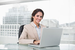 Happy businesswoman typing on laptop at her desk looking at camera Stock Photography