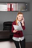 Happy businesswoman typing on laptop at her desk Stock Photo