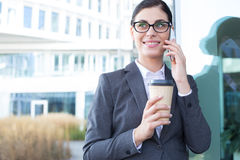 Happy businesswoman using cell phone while holding disposable cup outdoors Stock Photography