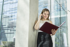 Happy businesswoman using cell phone while reading file in office Stock Photo