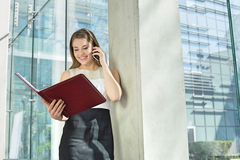 Happy businesswoman using cell phone while reading file in office Royalty Free Stock Image