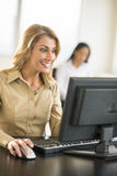 Happy Businesswoman Using Computer At Desk In Office. Happy young businesswoman using computer at desk in office with female colleague sitting in background Stock Photo