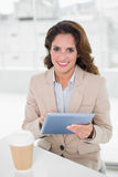 Happy businesswoman using digital tablet at her desk Royalty Free Stock Images