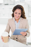 Happy businesswoman using digital tablet at her desk holding disposable cup Stock Photography