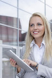 Happy businesswoman using digital tablet while looking away against office building Royalty Free Stock Photo