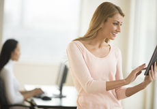 Happy Businesswoman Using Digital Tablet In Office Royalty Free Stock Images