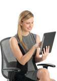 Happy Businesswoman Using Digital Tablet While Sitting On Chair Stock Images