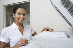 Happy Businesswoman Using Fax Machine In Office Royalty Free Stock Photo