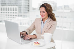 Happy businesswoman using laptop at her desk and having coffee Stock Photo