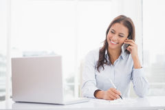 Happy businesswoman using laptop at her desk Stock Images