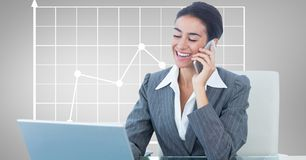 Happy businesswoman using laptop and mobile phone against graph Royalty Free Stock Photos