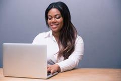 Happy businesswoman using laptop Stock Photo