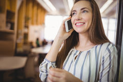 Happy businesswoman using mobile phone in office cafeteria Stock Image