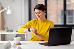 Happy businesswoman using smart watch at office royalty free stock photography