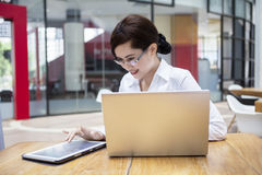 Happy businesswoman using tablet and laptop in cafe Stock Image