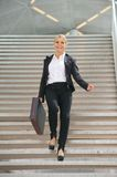 Happy businesswoman walking downstairs with briefcase Stock Photo