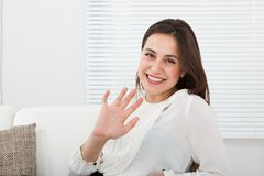 Happy businesswoman waving hand on sofa Royalty Free Stock Photography