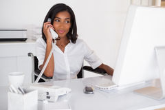 Happy businesswoman in wheelchair working at her desk Royalty Free Stock Photography