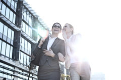 Happy businesswoman whispering in colleague's ear outside office building on sunny day stock images