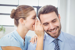 Happy businesswoman whispering to male colleague. Close-up of happy businesswoman whispering to male colleague in office Royalty Free Stock Images