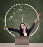 Happy businesswoman winning in 2013. Beautiful businesswoman is winning while sitting with her laptop in a classroom showing 2013 time Royalty Free Stock Photos