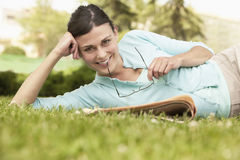 Free Happy Businesswoman With Newspaper Holding Spectacles While Lying On Grass Royalty Free Stock Images - 31832539