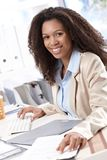 Happy businesswoman working at desk Stock Images