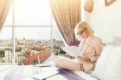 Happy businesswoman working with documents in hotel. Happy businesswoman working with documents. Female professional in hotel examining papers. Business lady go Royalty Free Stock Photography