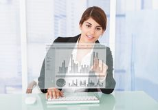 Happy Businesswoman Working On Graph At Computer Desk. Portrait of happy businesswoman working on graph at computer desk in office Royalty Free Stock Photo