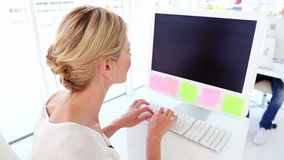 Happy businesswoman working at her desk. In her office stock footage