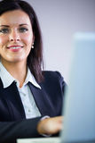 Happy businesswoman working at her desk Stock Image