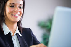 Happy businesswoman working at her desk Royalty Free Stock Photos