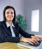 Happy businesswoman working at her desk Stock Photography