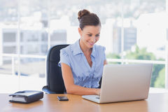 Happy businesswoman working on her laptop Stock Images