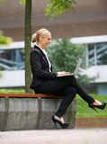 Happy businesswoman working on laptop in the city Royalty Free Stock Image