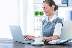 Happy businesswoman working on laptop computer Stock Photo