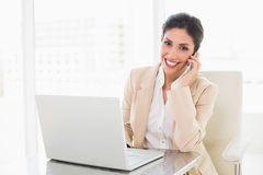 Happy businesswoman working with a laptop on the phone Stock Photography