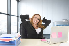 Happy businesswoman working at office laptop computer sitting on the desk relaxed Royalty Free Stock Photo